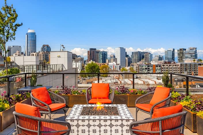 A gas fireplace burns on the rooftop patio with Seattle in the background.